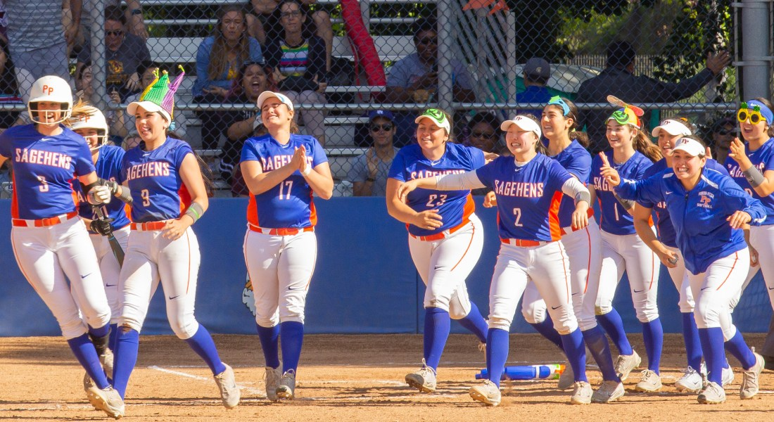 A group of eleven woman rush onto a softball field, wearing silly hats and celebrating their win.