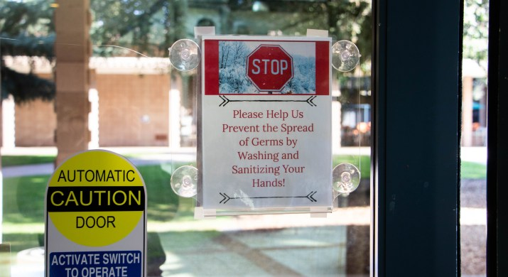 """A sign that says """"STOP: Please Help Us Prevent the Spread of Germs by Washing and Sanitizing Your Hands!"""" is displayed on a glass door next to another sign that says """"CAUTION: Automatic Door, Activate switch to operate."""""""