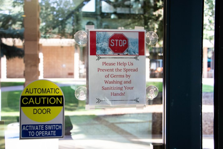 "A sign that says ""STOP: Please Help Us Prevent the Spread of Germs by Washing and Sanitizing Your Hands!"" is displayed on a glass door next to another sign that says ""CAUTION: Automatic Door, Activate switch to operate."""