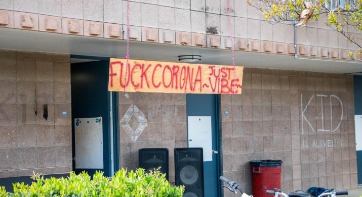 "A sign reading ""Fuck Corona Just -Vibe-"" hangs from a balcony."