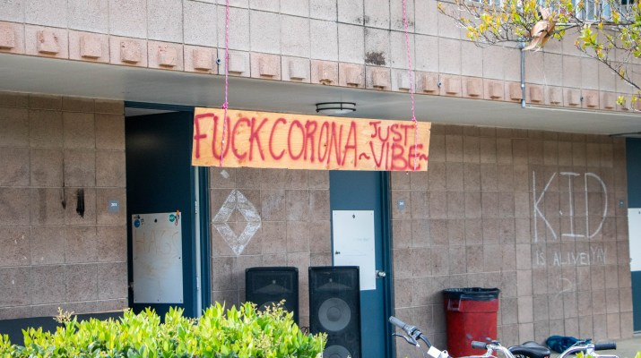 "A sign reading ""Fuck Corona Just -Vibe-"" hangs from a balcony."