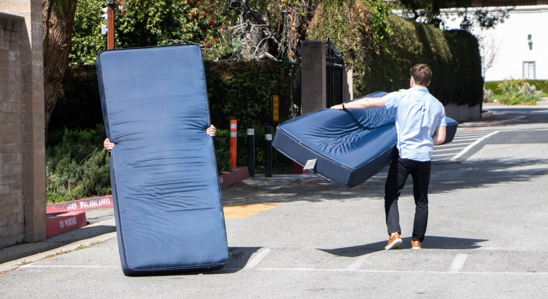 Two students carrying mattresses walk up a street.