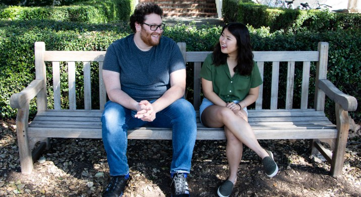 A man and a woman sit on a bench and smile at each other outside under a tree.