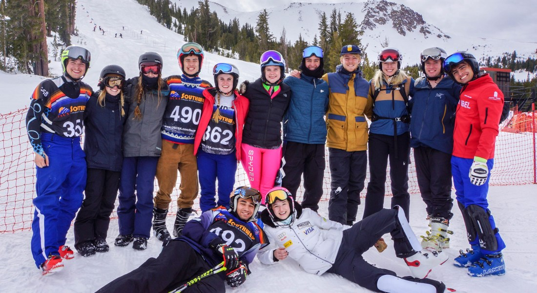 Thirteen students, eleven standing and two laying on the ground, wear ski coats, pants, and goggles with four wearing competition jerseys.