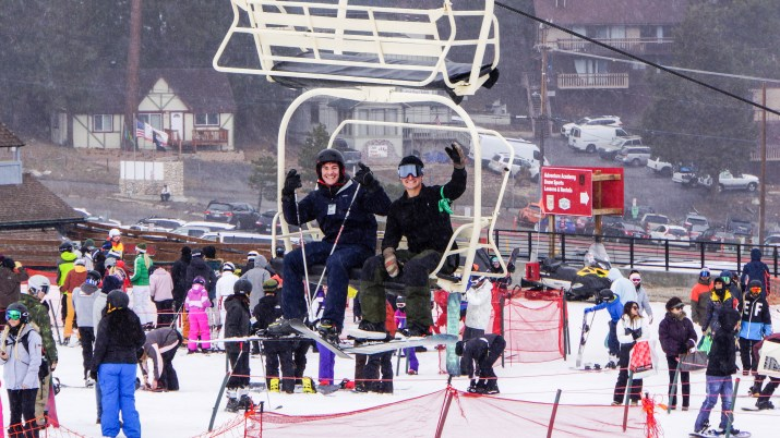 Two students, one with skiis and poles and the other with a snowboard, wave from a chair lift.