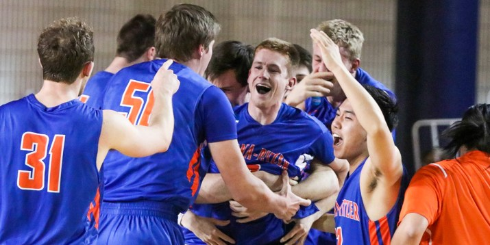 A group of basketball players embrace one central basketball player who smiles at the camera.