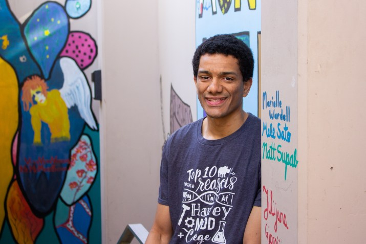 A man stands and smiles in the camera in the center of the image, surrounded by walls covered in art and graffiti.