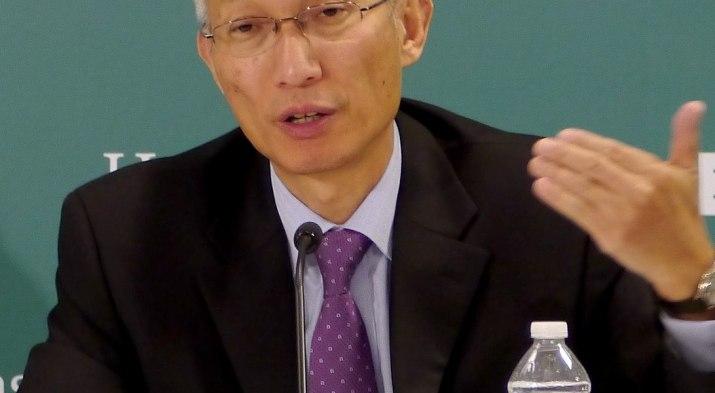 A man talks into a microphone.