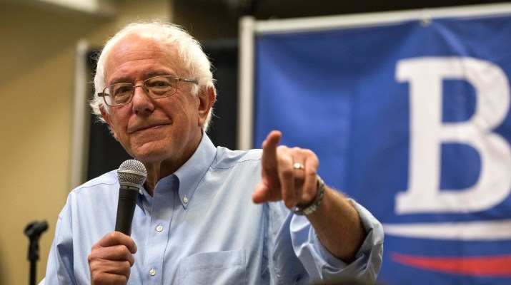 Bernie Sanders speaking at a campaign rally. He is holding a microphone in one hand and pointing at the audience with the other hand.