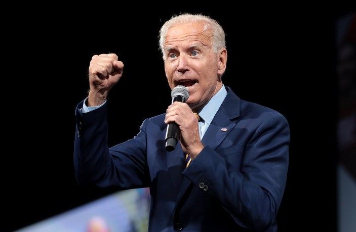 Joe Biden speaking at a forum. He is holding a microphone in one hand and holding his other hand up in a fist.