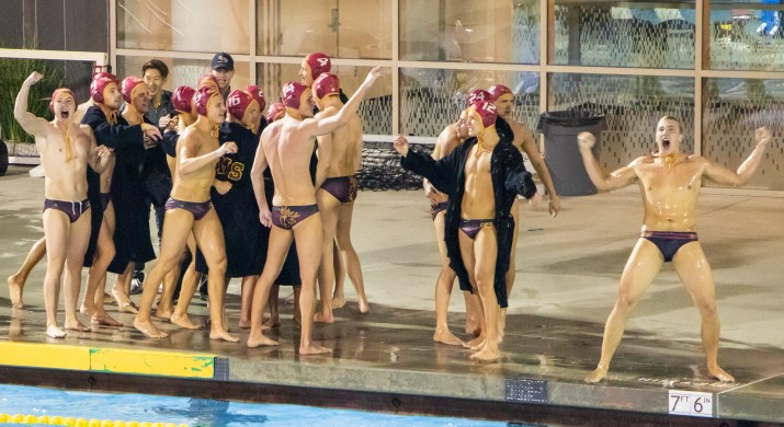 A group of male waterpolo players stand on the edge of the pool, cheering and grabbing each other in celebration.