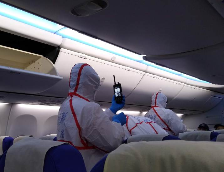 Quarantine=staff-in-hazmat-suits-screening-passengers-on-plane