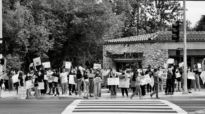 protestors hold signs on a street corner in Claremont