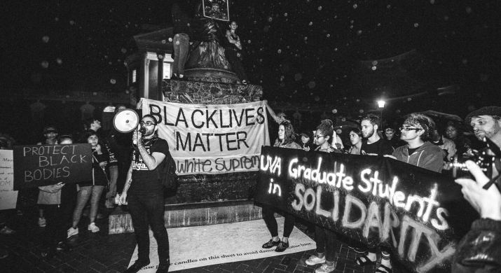 """a man with a megaphone at a protest. signs read """"Black Lives Matter"""" and """"UVa Graduate Students in Solidarity"""""""