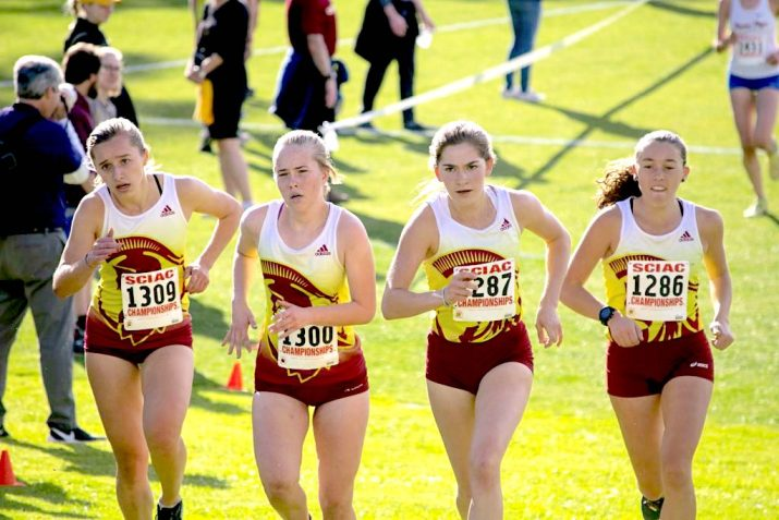 Four women run in a cross country tournament. They wear white tank tops and red shorts.