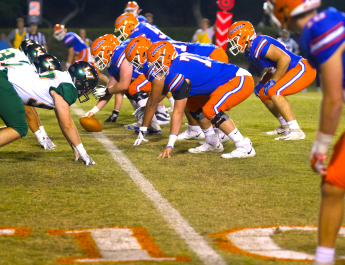 A line of football players hunch before a play.