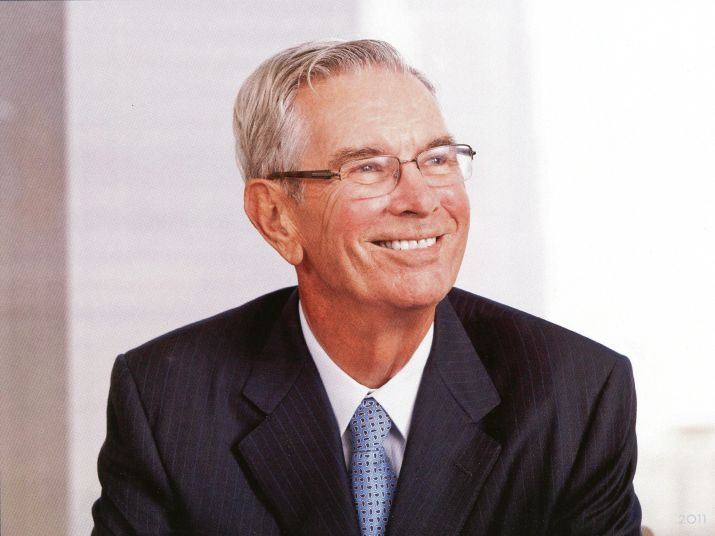 a smiling man with grey hair, glasses and a suit
