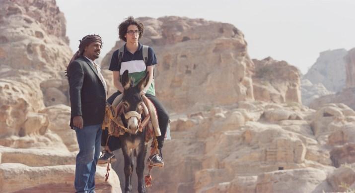A man stands next to a boy on a donkey.
