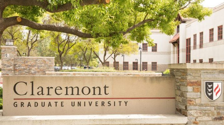 """An academic quad is in the background and a cement and stone wall in the foreground reads """"Claremont Graduate University."""""""