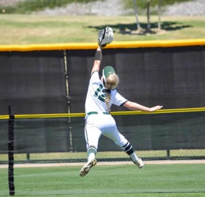 A softball player jumps into the air to catch a ball.