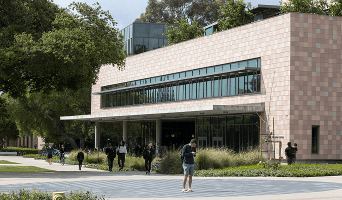 College students walk along a paved path. On their right is a tan tile and glass building. Plants and trees surround the building and path.