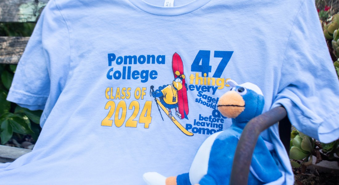 """A blue and orange sagehen stuffed animal sits on a shirt reading """"Pomona College Class of 2024""""."""