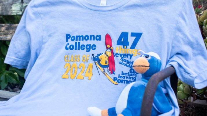 "A blue and orange sagehen stuffed animal sits on a shirt reading ""Pomona College Class of 2024""."