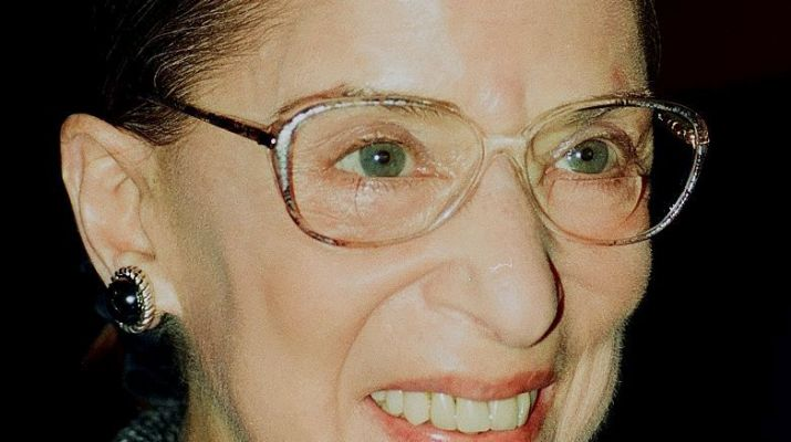 A woman with glasses smiles off camera.