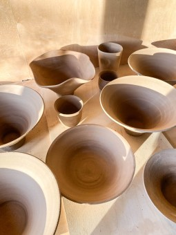 Mulitple beige pots, bowls, and cups sit on a table.