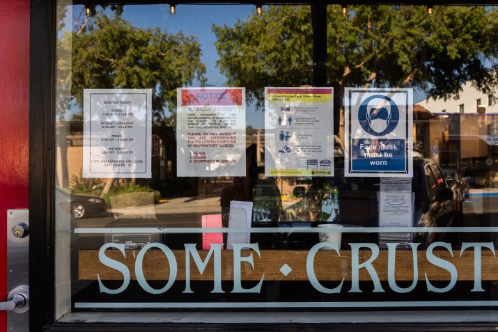 Front of business named Some Crust with various flyers taped on the glass wall