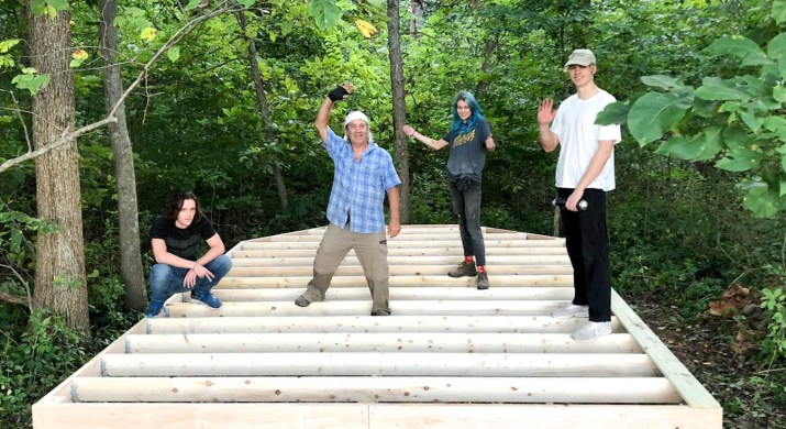 Four people stand on wood planks in the forest.