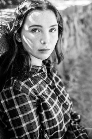 A girl wearing a plaid shirt looks at the camera.