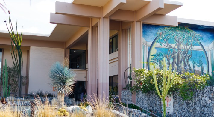 The exterior of Pitzer College's dining hall. The large tan building has a mural on one side depicting an orange tree and some people. The building is surrounded by plants and cacti.