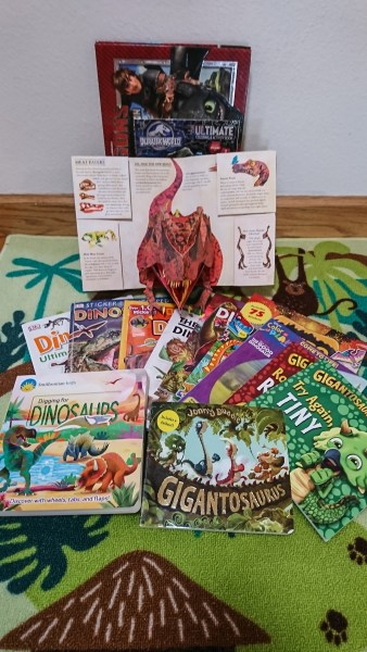 Multiple dinosaur books sit on a green carpet.