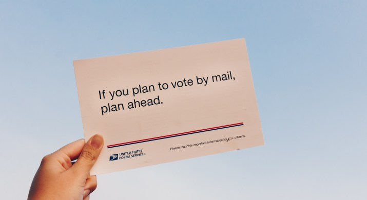 """A hand holds up a post card reading """"If you plan to vote by mail, plan ahead."""" against a gray-blue sky."""