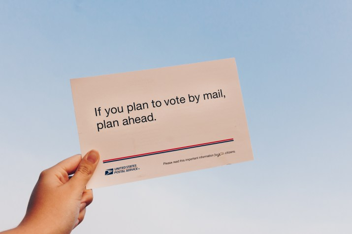 "A hand holds up a post card reading ""If you plan to vote by mail, plan ahead."" against a gray-blue sky."
