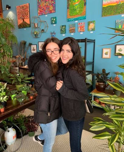 A photo of two female college students embracing for a photo. They stand in a store with many plants and colorful art pieces for sale.