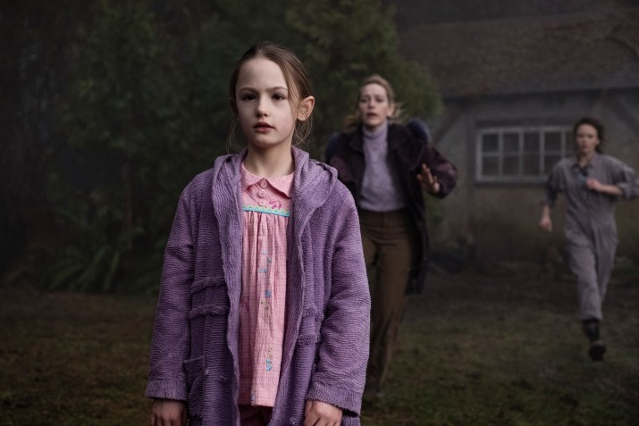 A young girl in a purple coat emptily stares off screen while two adult women rush towards her in the background.