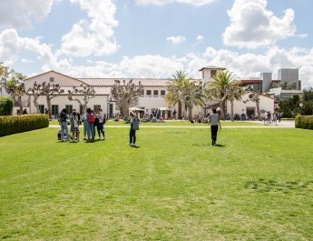 Many students stand on a green quad in front of a long white building.