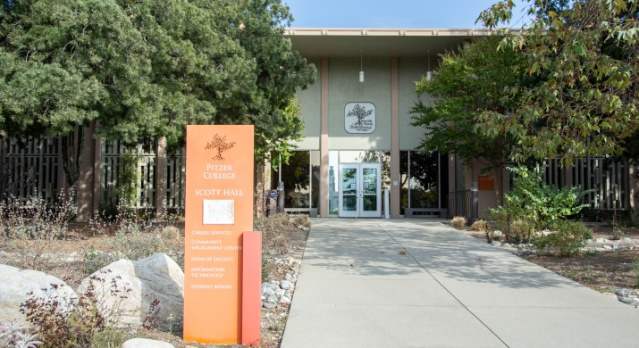 Orange sign that says Pitzer College in front of building flanked by trees