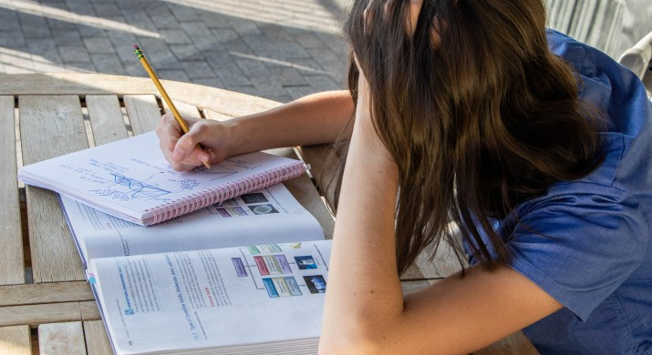 A student leans their head on their hand while taking notes.