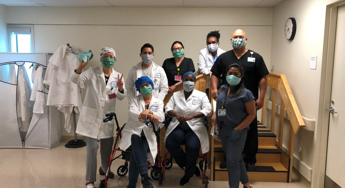 Eight medical workers pose for a photo while wearing handmade masks.