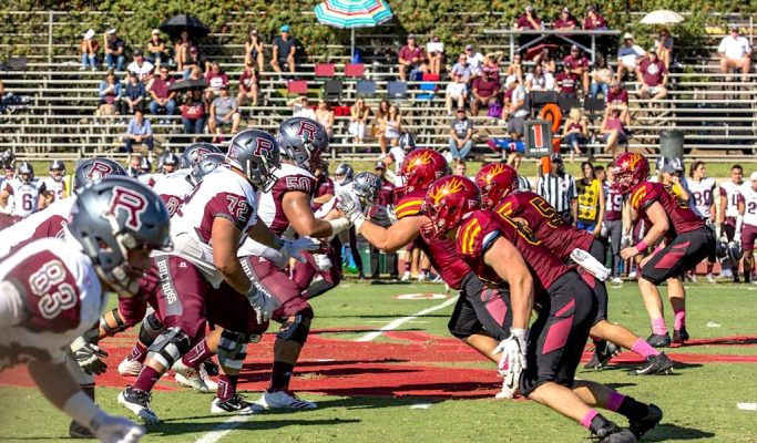 Players from the CMS and University of Chapman football teams face off against each other during a game.