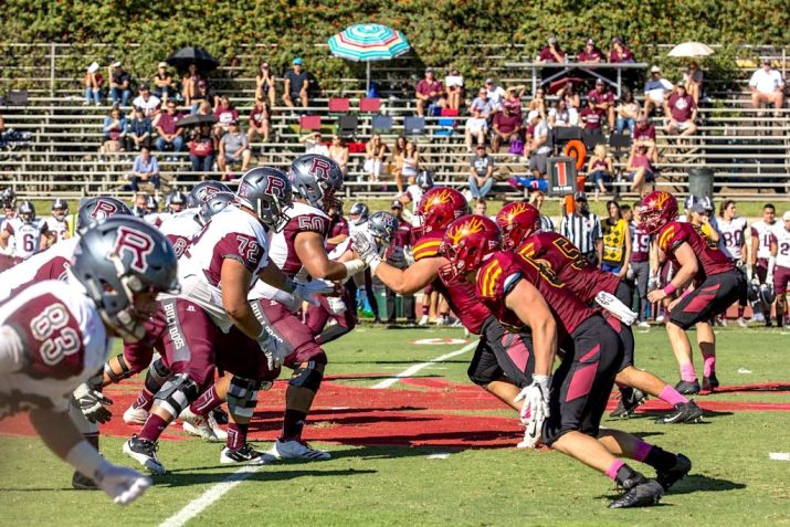 Players from the CMS and University of Redlands football teams face off against each other during a game.