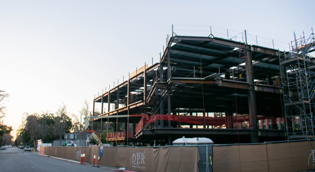 A scaffolded building is surrounded by a brown contraction fence.