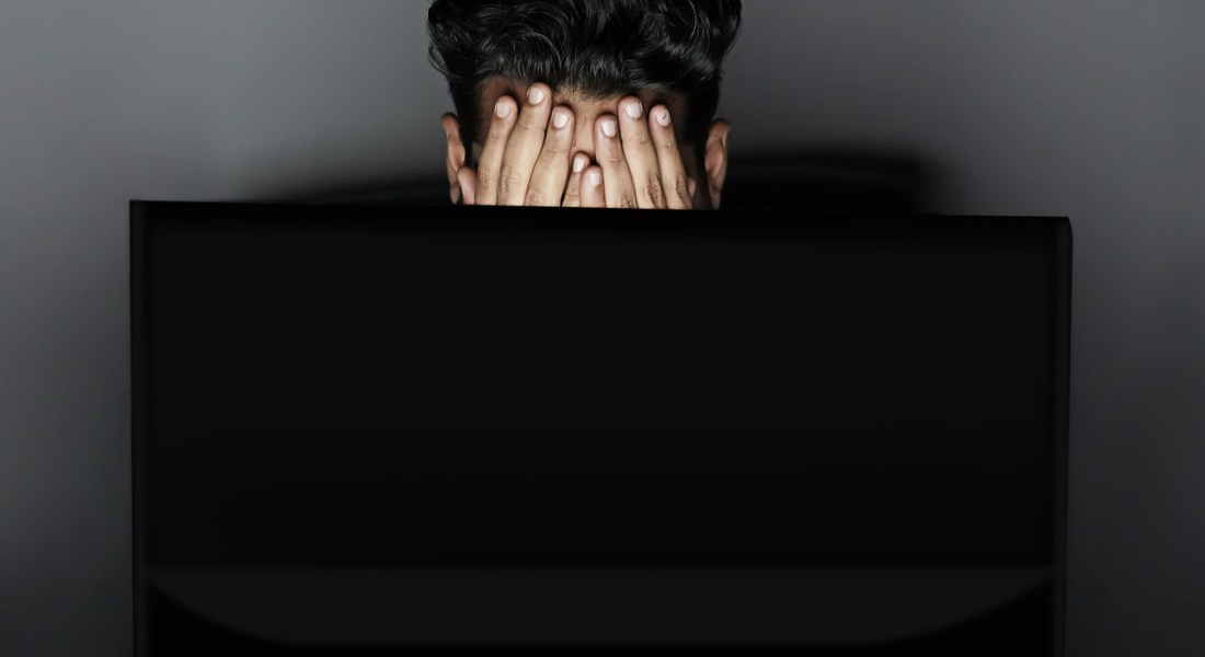 A man buries his face in his hands as he sits in front of his computer screen in a dark room.