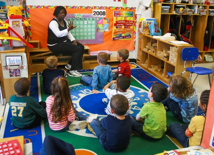 A teacher teachers a group of kindergarten students.