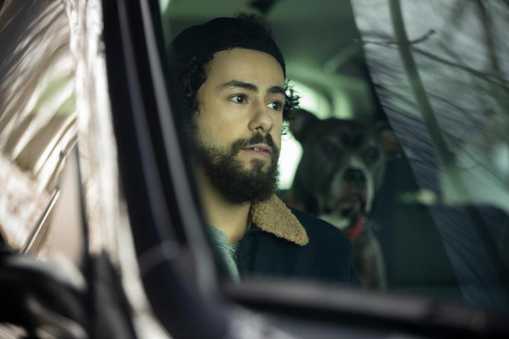 A man sits in a car with a dog.