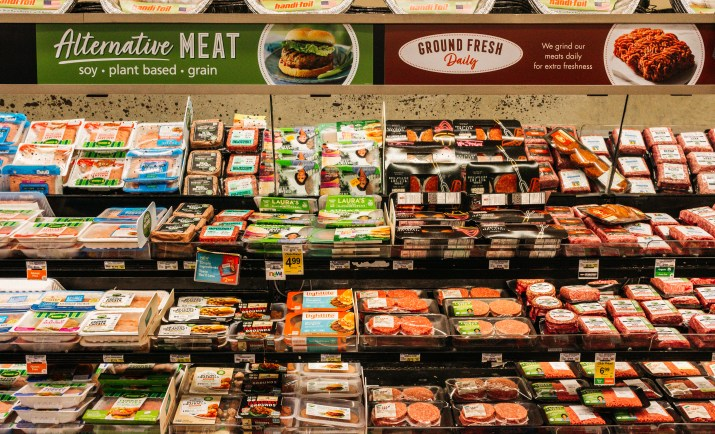 Three shelves in the grocery store are covered in all types of meat.