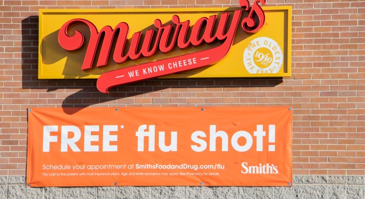 """A sign that says """"Free Flu Shot"""" is on a white building under a red and orange """"Murrays"""" sign."""